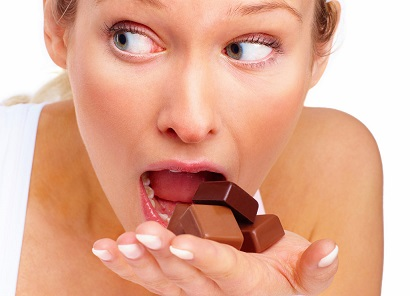 Young cute woman trying to eat chocolates over white background